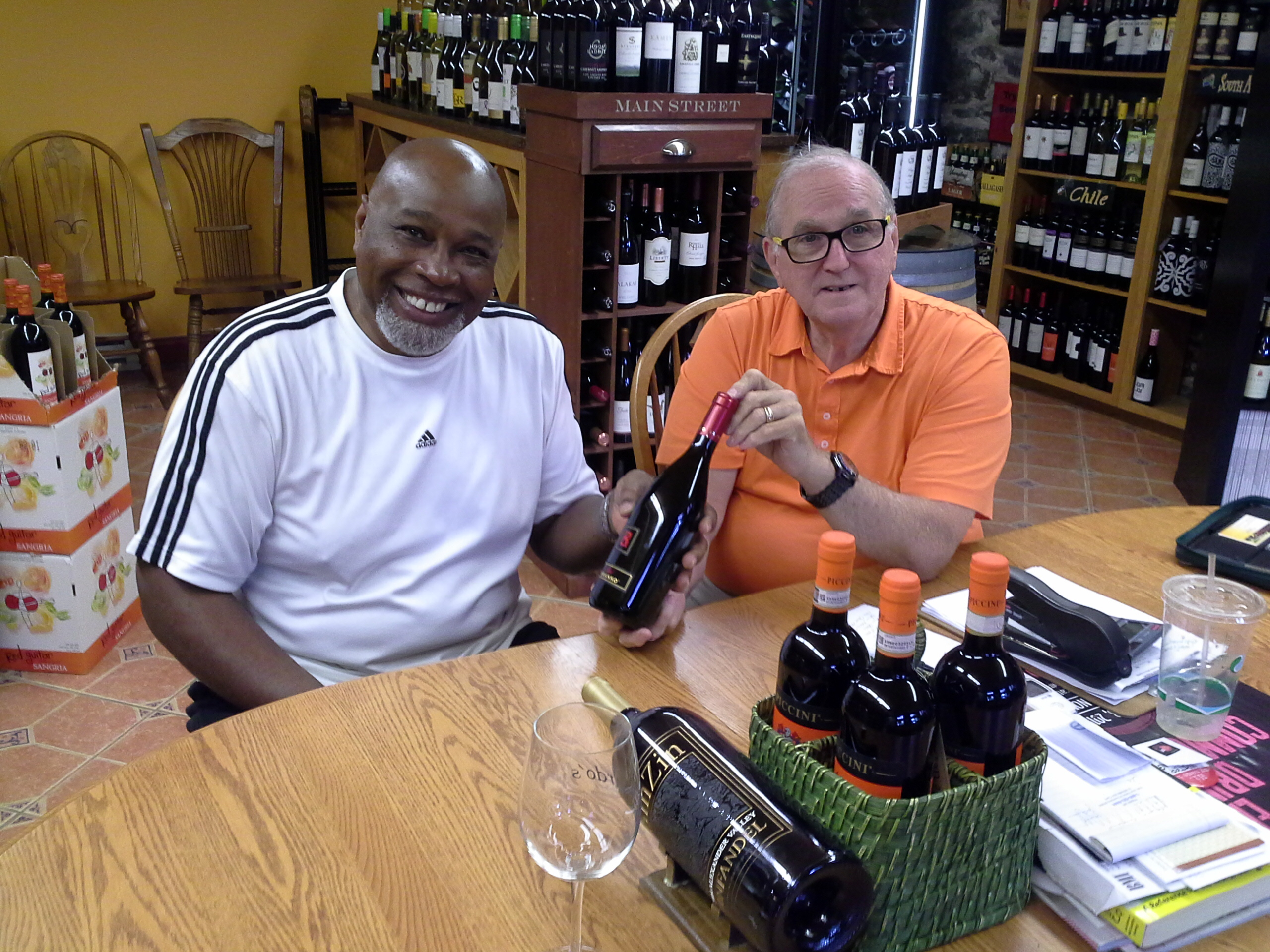 Bump City Wine Co. founder Roger Smith, left, visits with Richard Rourke at Tutto Bene Wine & Cheese Cellar in downtown Lowell.
